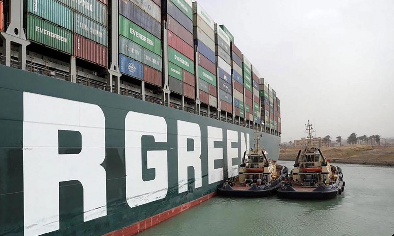Các tàu kéo cố gắng giải phóng tàu hàng Ever Given mắc kẹt giữa kênh đào Suez hôm 25/3. (Ảnh: AFP)