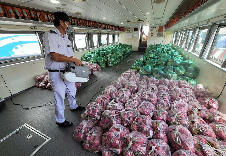Nhân viên tàu khử khuẩn hàng hóa. Ảnh: Hoàng Thanh.